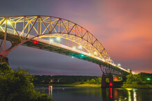 Brightly Lit Sagamore Bridge In Stormy Weather At Dawn. Vivid Light Reflections On The Cape Cod Canal With Dimly Glowing Red Clouds In The Sky.