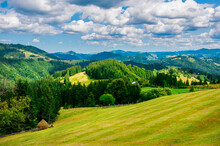 Pastures Of Young Green Grass On The Slopes Of The Mountains Against The Backdrop Of A Beautiful Blue Sky. High Quality Photo