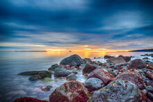Rocky Shore Surrounded By The Sea Under A Cloudy Sky During The Sunset