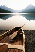 Wood Canoe On The Edge Of Bowman Lake At Sunrise In Glacier National Park, Montana