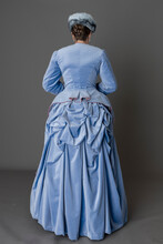 A Victorian Woman Wearing A Pale Blue Velvet Bustle Ensemble With A Fur Hat And Muff
