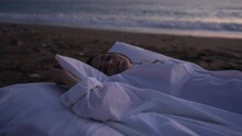 Portrait Of Relaxed Joyful Caucasian Young Woman Lying On Bed With Closed Eyes As Foamy Sea Ocean Waves Rolling At Background In Twilight. Happy Carefree Lady Sleeping On Cushioned Pillows At Sunset