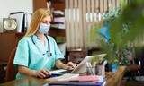 Professional general practitioner woman in mask working sitting at working place in office behind laptop