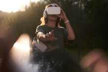 A Girl Holding Virtual Reality Glasses On Her Head With Her Hands. He Stretches Out One Hand To The Camera, Next To A Beam Of Sunlight. High Quality Photo