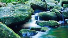 Slowmotion Small Waterfall Cutting Through Boulders