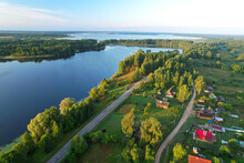 Lake Among Green Trees In The Countryside. Aerial View Of A Large Lake Or River Against A Blue Sky. Ecology And Wetlands Concept