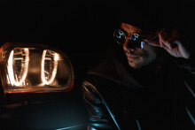 Fashion Cool Man With Sunglasses In Stylish Leather Jacket Sits Near Headlight At Night. Male Silhouette In The Dark