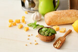 Bowl with tasty pesto sauce, cheese and pine nuts on light wooden background