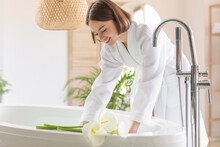 Young Woman Running Bathtub With Warm Water At Home
