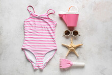 Set Of Beach Accessories For Children, Stylish Swimsuit And Starfish On Light Background