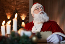 Pensive Aged Santa Claus In Eyeglasses Sitting At Table And Looking Up While Writing Letter