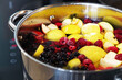 We are preparing a delicious compote from apples, cherries, raspberries, irgi. Fresh fruits and berries are boiled in a metal pan on the stove.