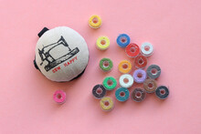 Sewing Machine Bobbins With Colorful Thread And A Pincushion On A Pink Background