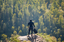 Active Healthy Athlete Male In Black Sportswear And Cap Holding Backpack Standing On High Mountain With Trees Of Forest On Background During Outdoor Leisure Hiking Activity Lifestyle Recreation