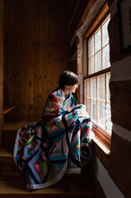 Young Boy Wrapped In A Quilt Looking Out The Window Of A Log Cabin.