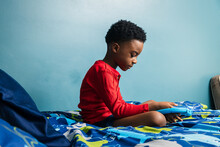 Boy Using Digital Tablet On His Bed