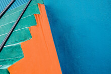 Abstract Shot Of Green Steps At Painted Blue And Orange Wall