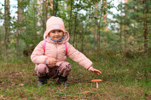Little Girl In A Pink Hat And Jacket In The Forest Next To A Poisonous Mushroom Fly Agaric, Poisoning With Inedible Mushrooms.