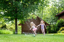 Two Cute Little Girls Playing Outdoors In A Water Sprinkler.