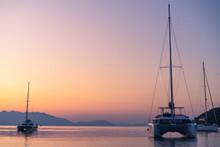 Yacht With Greek Flag In Mediterranean Sea On A Pink Sunrise