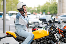 Right Side Shot Of A Young Woman Riding A Motorcycle Fastening Her Protective Helmet