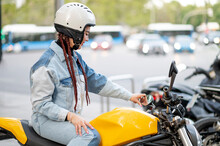 Right Side Shot Of A Young Woman Riding A Yellow Motorcycle