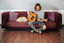 Attractive Man With Long Hair Playing Acoustic Guitar Indoor With Dog