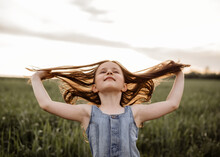 Happy 5 Years Old Girl In A Green Wheat Field With Long Hair At Sunset