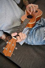 A Young Man Plays A Wooden Ukulele