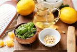 Bowl with tasty pesto sauce, pine nuts and lemon on table, closeup