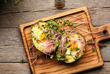 Board with stuffed avocado and micro green on wooden background