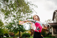 A Little Girl Plays Outside In Butterfly Wings With Arms Outstretched