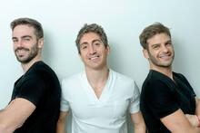 Grupo De 3 Hombres Sonrientes Delante De Una Pared Blanca. Equipo De Odontólogos En Una Clínica