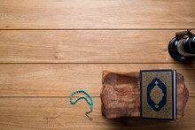Islamic Concept - The Holy Al Quran With Written Arabic Calligraphy Meaning Of Al Quran And Rosary Beads Or Tasbih And An Arabian Lamp, On Wooden Stand, With Copy Space.