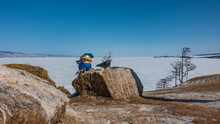 Picturesque Boulders Lie On The Ground, On The Shore Of A Frozen Lake. A Pigeon Is Sitting On A Rock. Nearby, A Pillar Is Visible, Tied With Ritual Multicolored Ribbons. Baikal.