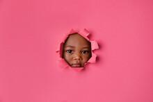 Little Girl's Face Peeking Through Pink Torn Paper