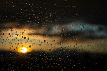Window Glass After Rain With Water Drops.  Background Of Stormy Sunset Sky.