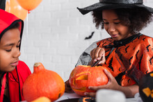Happy African American Girl In Pointed Hat Carving Pumpkin Near Brother