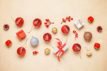 Beautiful Christmas Composition. Red And Gold Christmas Balls, Gift Boxes And Decorations On A Beige Concrete Background. Top View, Flat Lay.