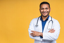 Portrait Of Young African American Indian Black Doctor With Stethoscope Over Neck In Medical Coat Standing Isolated Over Yellow Background.