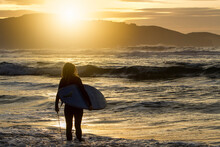 Anonymous Woman With Surfboard Getting Into The Sea During Sunset