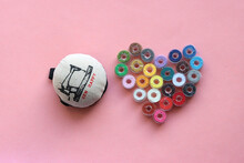 Sewing Machine Bobbins With Colorful Thread Forming The Shape Of A Heart, And A Pincushion On A Pink Background