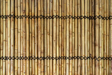 Background Of Binded Yellow Bamboo Wall With Black Rope