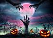Leinwandbild Motiv Zombie Hands Rising Out Of A Graveyard With Full Moon And Halloween Pumpkins