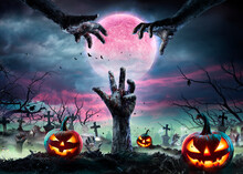 Zombie Hands Rising Out Of A Graveyard With Full Moon And Halloween Pumpkins