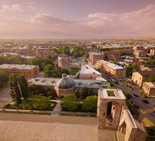 Aerial View Of Open Air Altar With Seminary And Church Of Archangels In Etchmiadzin Complex At Sunset