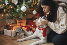 Stylish Woman In Cozy Sweater Caressing Adorable Dog Under Christmas Tree With Gifts And Lights. Happy Young Female Hugging And Kissing Cute White Dog In Festive Scandinavian Room. Happy Holidays