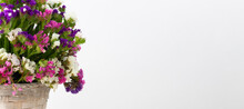 Basket With Multicolored Flowers Of Statice Stands On A Light Gray Background . The Flowers Are Purple, White And Pink . Banner With Free Space For Your Business .