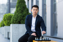 Serious Asian Man Playing Chess Outside, Businessman Thinking Playing Chess Sitting On Bench Near Office Center