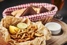 Crunchy Fried Anchovies Snack Served With Lemon, Lime And Garlic Sauce Served On Crumpled Paper